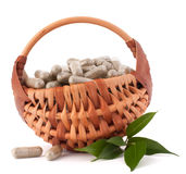 Herbal drug capsules in wicker basket. Alternative medicine conc Royalty Free Stock Images