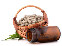 Herbal drug capsules in wicker basket. Alternative medicine conc Stock Photo
