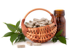 Herbal drug capsules in wicker basket. Alternative medicine conc Stock Photos