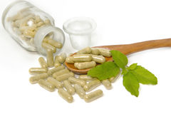 Herbal drug capsules in wooden spoon Royalty Free Stock Photos