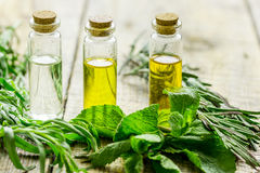 Herbal extract in glass bottles, mint and rosemary for spa on wooden table background Stock Photo