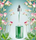 Herbal facial serum bottle with pipette and flowers plats on blue background stock photography