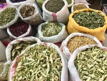 Herbal health treatment cure plants, spices cinnamon stick daisy at open air bazaar, market.  Royalty Free Stock Image