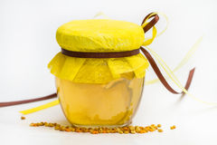 Herbal honey isolated. Herbal honey in jar with small honeycomb and herbs isolated on white background royalty free stock photo