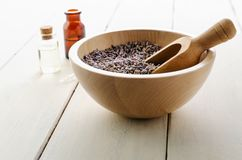 Herbal Lavender Buds in Wooden Bowl with Glass Bottles containing Oils on Wood Plank Table royalty free stock images