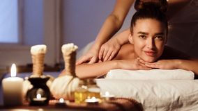 Herbal massage. Woman relaxing in spa salon. And looking at camera stock photography