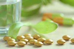 Herbal medicine. Pills on the table on green background stock images