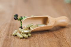 Herbal medicine capsules from herb on rustic wooden. Table for healthy eating and good life ,soft focus Royalty Free Stock Photo