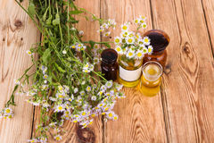 Herbal medicine concept - bottles with camomile and oil on woode Royalty Free Stock Images