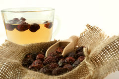 Herbal medicine. Cup of herbal tea with dried rose hips in a sack Stock Photo