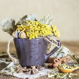 Herbal medicine, homeopathy, the collection of medicinal herbs for tea and medicines. Dried tansy flowers and oak leaves in a cup. On the background of a wooden stock photos