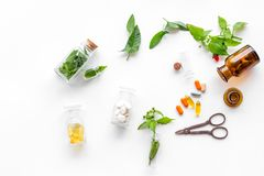 Herbal medicine. Leaves, bottles, pills and sciccors on white background top view Royalty Free Stock Images