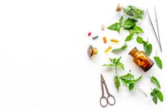 Herbal medicine. Leaves, bottles, pills and sciccors on white background top view copyspace Royalty Free Stock Photography