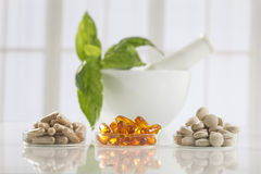 Herbal medicine pills and mortar over bright Royalty Free Stock Photography