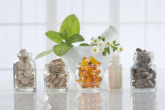 Herbal medicine pills and mortar over bright Stock Photo