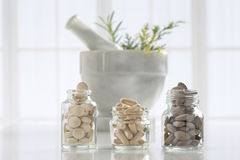 Herbal medicine pills and mortar over bright Stock Photos
