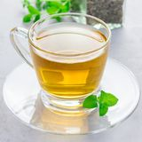 Herbal mint tea in glass cup with fresh peppermint on background, square format Stock Images