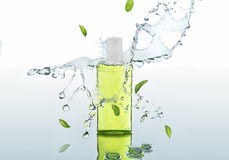 The herbal  moisturizing shampoo stands on the water background with splashes and mint leaves Stock Images