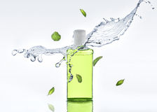 The herbal moisturizing shampoo stands on the white background with water splash and mint leaves Stock Images