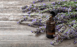 Herbal oil and lavender flowers bouquet on wooden background Stock Photo