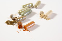 Herbal Pills. Herbal medicine capsules. Some opened with herbal powder falling out Royalty Free Stock Images