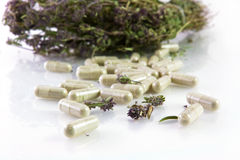 Herbal pills and dry thyme. Close-up Royalty Free Stock Images