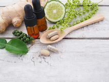 Herbal pills in wooden spoon and herbs stock photo