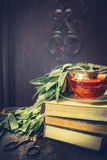 Herbal sage tea with herbs leaves , stack of books and old pair of scissors over rustic wooden background. Retro toned royalty free stock photo