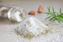 Herbal salt in glass jar. Sea salt with aromatic herb - rosemary and garlic. Copy space royalty free stock photo