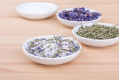 Herbal salt with rosemary and lavender. Herb salt with rosemary and lavender blossoms on a wooden background Stock Photos