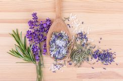 Herbal salt with rosemary and lavender. Top view of a spoon with herbal salt of rosemary and lavender blossoms on a wooden background Stock Photography