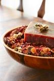 Herbal Soap. Handmade herbal soap in a bowl of dried rose petals stock image