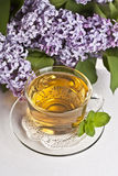 Herbal tea. Cup of fresh herbal tea with lilac in the background Royalty Free Stock Photo
