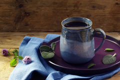 Herbal tea against cold with fresh sage and mint in a blue mug o. N plate and napkin on a rustic wooden table, health care concept, home remedies to strengthen Royalty Free Stock Images