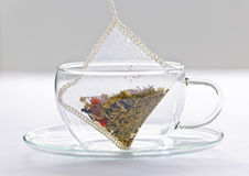Herbal tea bag in glass cup. Glass teacup with soothing herbal tea in silk bag stock photography
