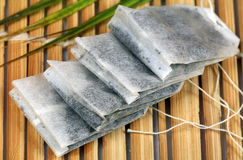 Herbal tea bags. Stacked on wooden background stock photography