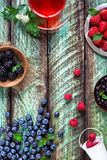 Herbal Tea and berries on green rustic table Royalty Free Stock Images