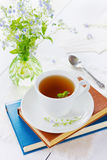 Herbal tea with books and flowers Stock Photos