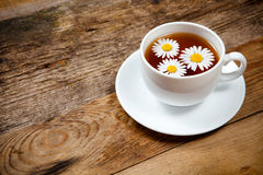 Herbal tea with chamomile on old wooden table Stock Photos