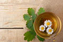Herbal tea with chamomile on old wooden table. Top view. alternative medicine concept.  Royalty Free Stock Photo