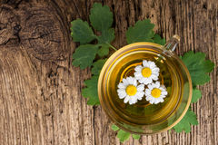 Herbal tea with chamomile on old wooden table. Top view. alternative medicine concept.  Royalty Free Stock Images