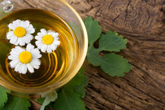 Herbal tea with chamomile on old wooden table. Top view. alternative medicine concept Stock Images