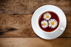 Herbal tea with chamomile on old wooden table Royalty Free Stock Image