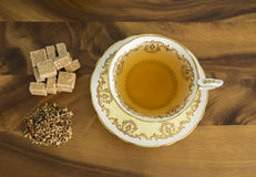 Herbal Tea in a classic cup. Herbal tea in an old fashioned cup and saucer with raw sugar cubes and loose leaf tea. wood background Royalty Free Stock Images