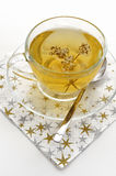 Herbal tea in clear glass cup. And saucer with a spoon on a gold and silver star covered napkin Stock Photos