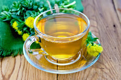 Herbal tea in a cup with a bouquet of Rhodiola rosea on the boar Stock Photos