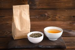 Herbal tea in cup. A paper bag of herbs and a cup of hot drink. Wooden background stock images
