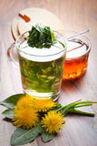 Herbal tea with dandelion leaf in tea cup, on wooden table Stock Photo