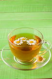 Herbal tea with fresh chamomile flowers on green wooden background with copy space for your text Royalty Free Stock Images