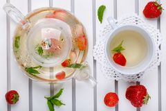 Herbal tea with fresh strawberry and mint. Hot beverage in glass teapot and cup on white tray, top view royalty free stock photography